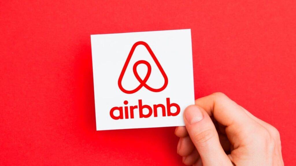 Imagen del logo de AirBNB cargado por una mano